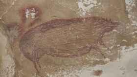 Dos manos y la representación de un cerdo.