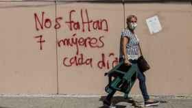 Una mujer camina frente a una pared con el mensaje: Nos faltan 7 mujeres cada día, en Ciudad de Guatemala.