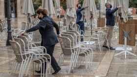 Camareros recogen una terraza en una plaza de Castilla y León. Efe