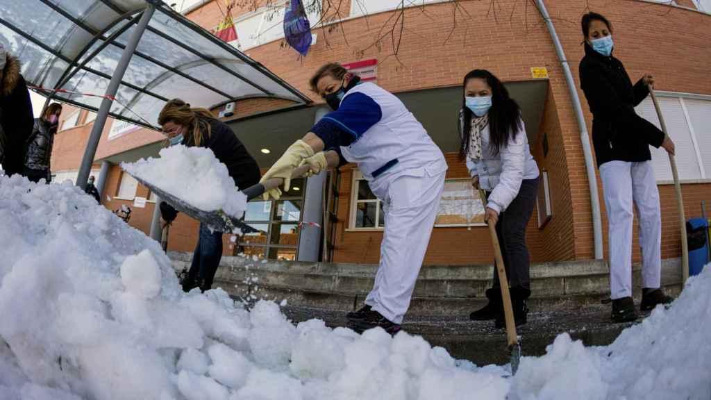 Personal de limpieza, junto a madres y padres, retiran hielo y nieve en el colegio Angel León, Colmenar Viejo, Madrid.
