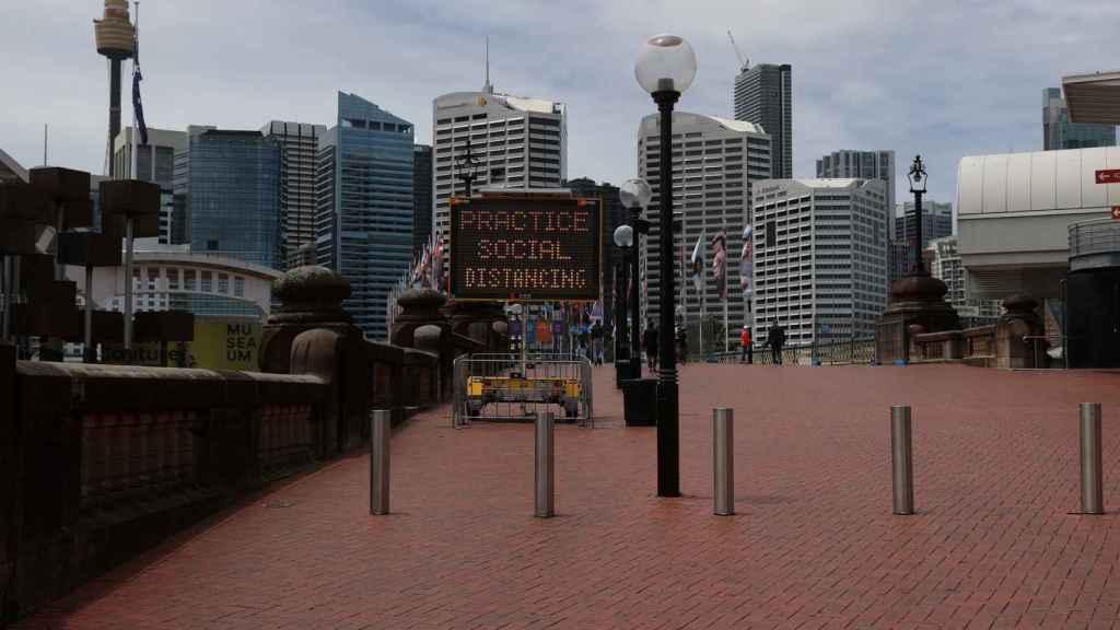 Un cartel advierte en Sidney de la necesidad de mantener las distancias.