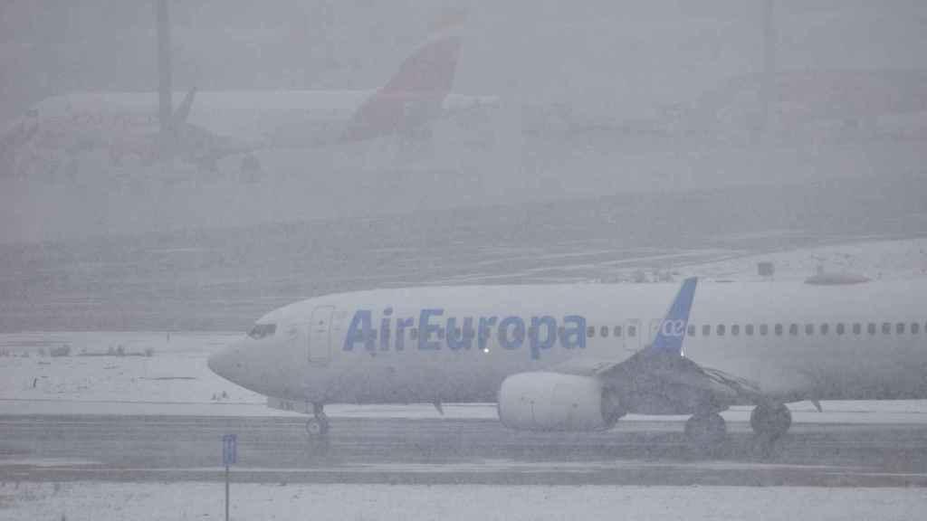 Un avión en Barajas en un día de nieve.