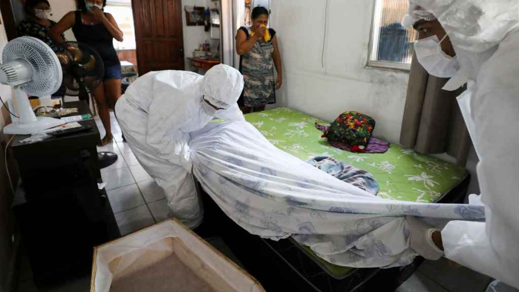 Trabajadores de una funeraria de Manaos retiran el cuerpo de una persona fallecida en su casa por coronavirus.