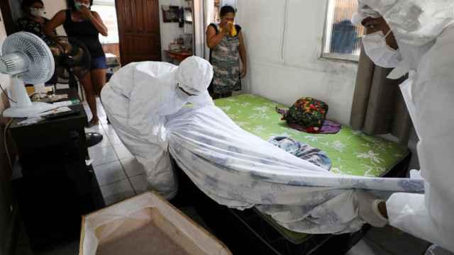 Trabajadores de una funeraria de Manaos retiran el cuerpo de una persona fallecida en su casa.