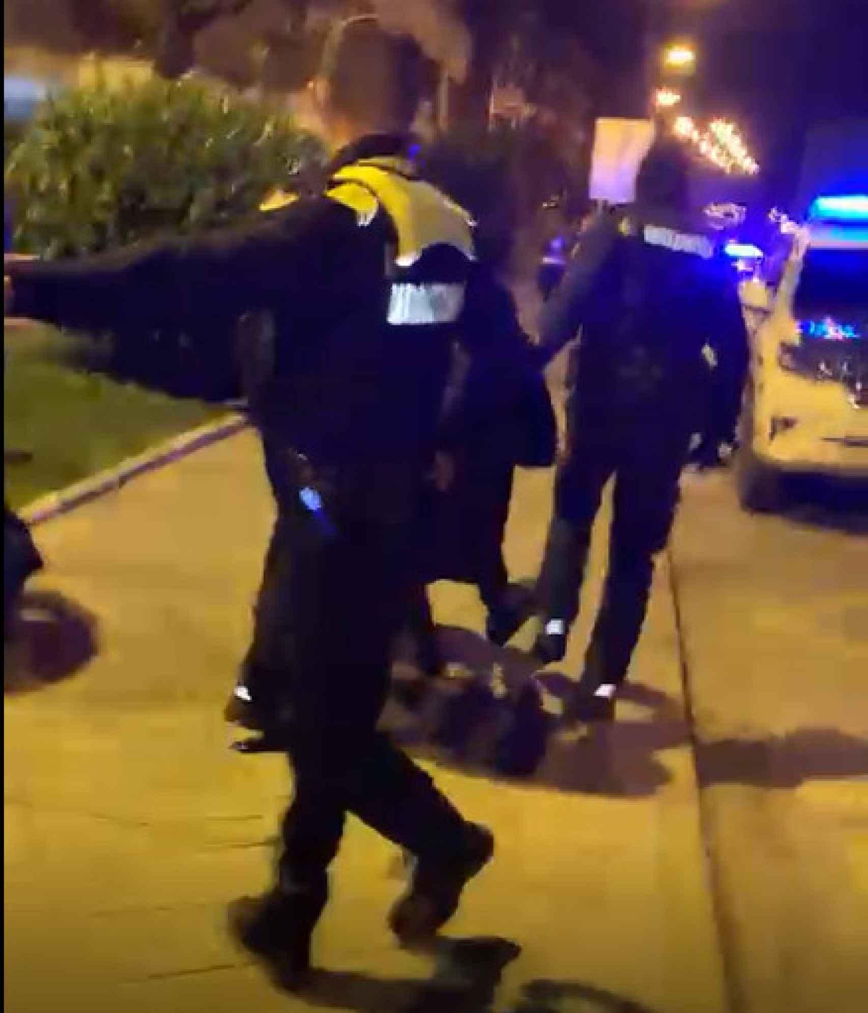 Un policía local de Munguía trata de retener a los jóvenes iracundos mientras sus compañeros conducen a un detenido a un coche patrulla.
