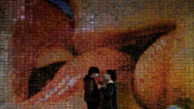 Dos jóvenes con mascarilla ante el mural de Joan Fontcuberta en Barcelona.