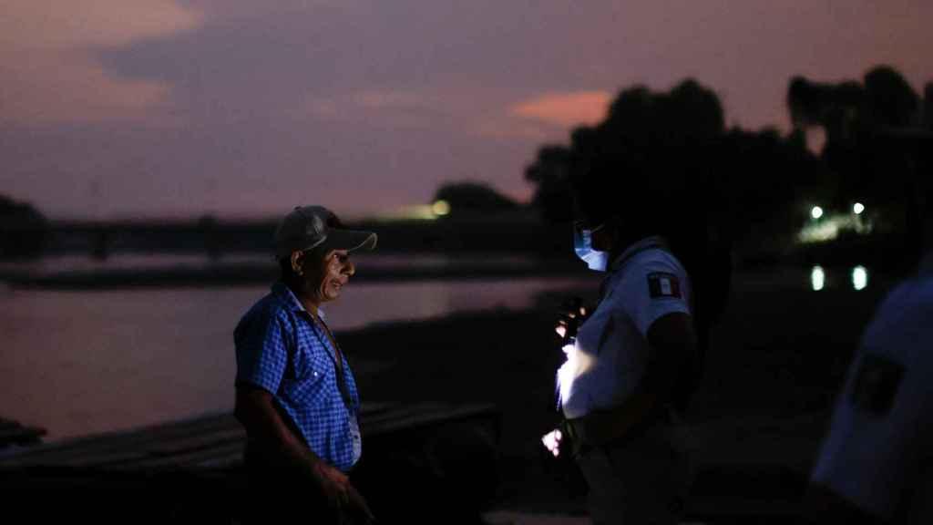 Un policia pide la documentación e una hombre junto al río Suchiate.