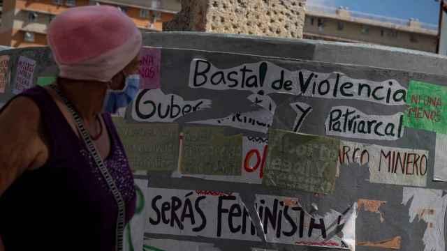 Una mujer camina frente a una pared con varios mensajes a favor del aborto en Caracas.