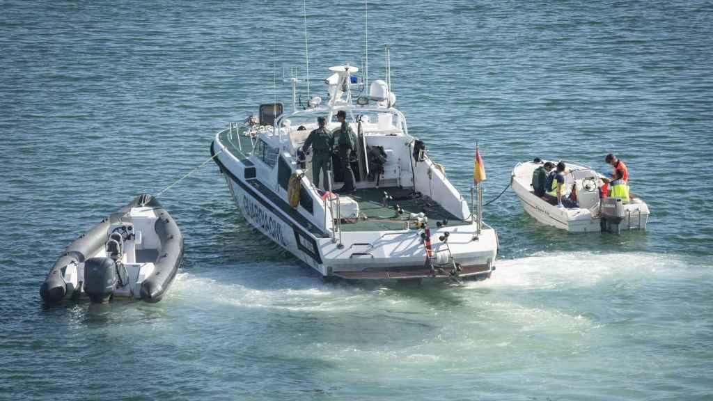Una patrullera de la Guardia Civil traslada hasta el puerto de Algeciras la lancha (i) y la barca en la que navegaban el menor fallecido y su padre, el 14 de mayo de 2018.