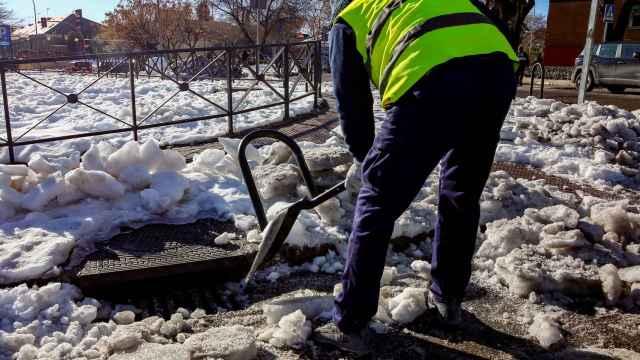 Un operario limpia nieve del alcantarillado de Madrid antes de que comiencen las lluvias en la capital.