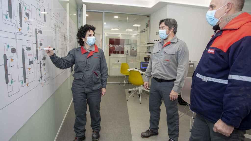Esther González repasa las tareas con varios trabajadores de la planta química.