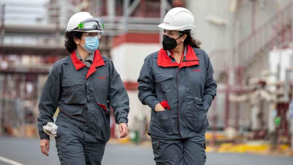 Esther González y una de las mujeres que ocupa un puesto de mano en la planta química.