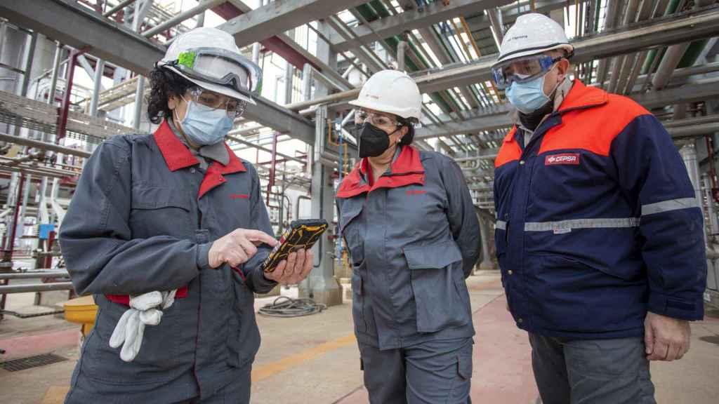 Esther González junto a dos trabajadores, dentro de una de las instalaciones de la planta.