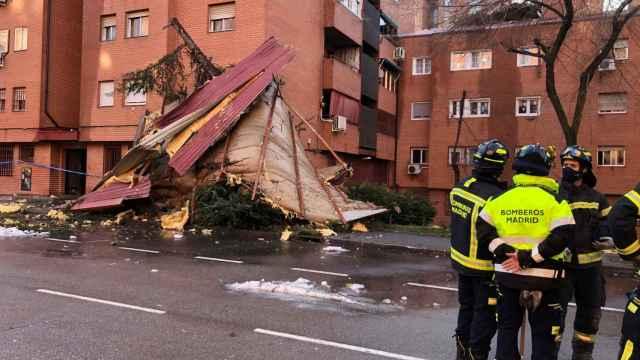 Efectivos del Cuerpo de Bomberos de Madrid intervienen este viernes en la caída de dos faldones de cubierta por el fuerte viento.
