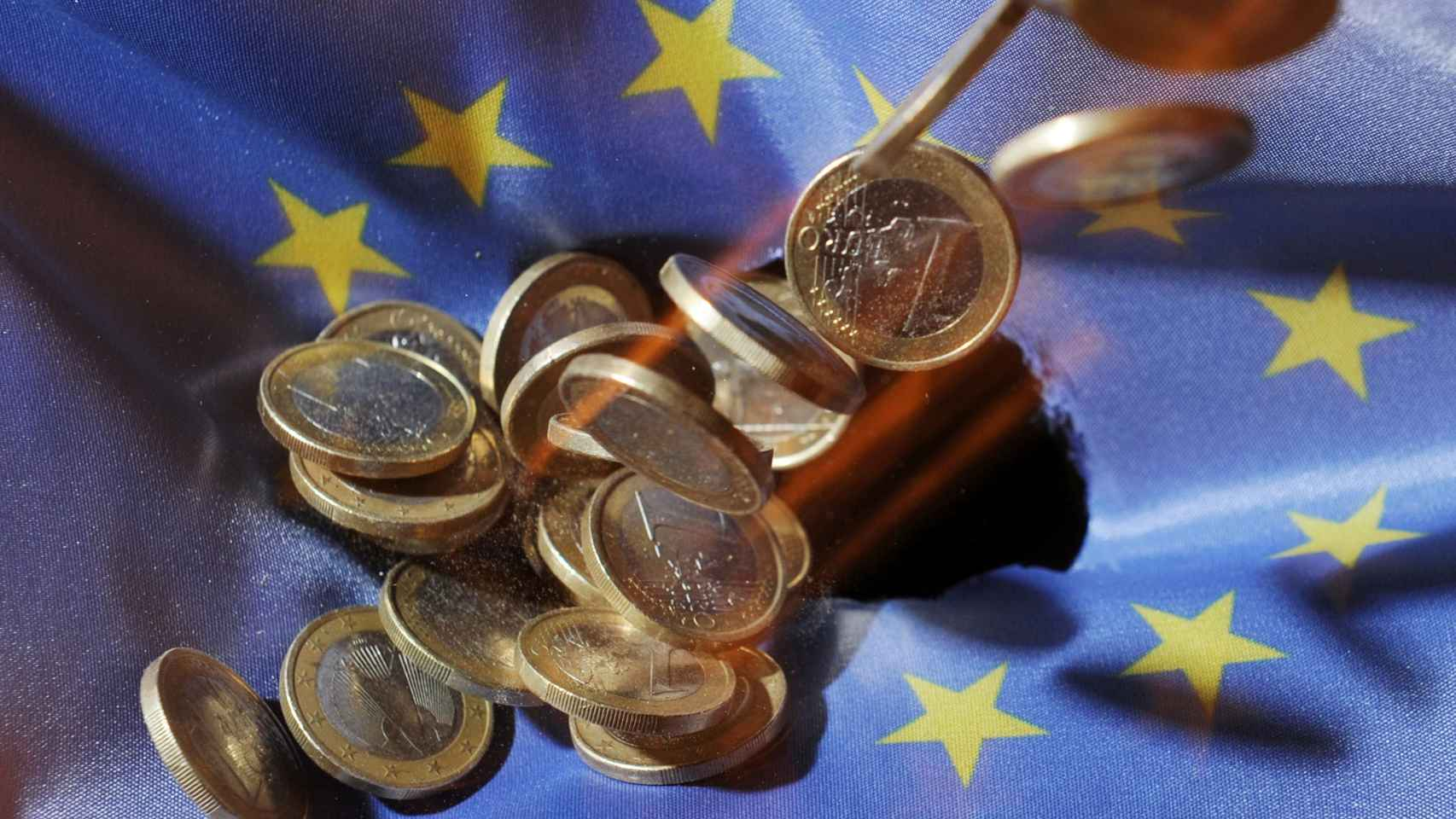 Varias monedas de euro sobre una bandera de la Unión Europea.