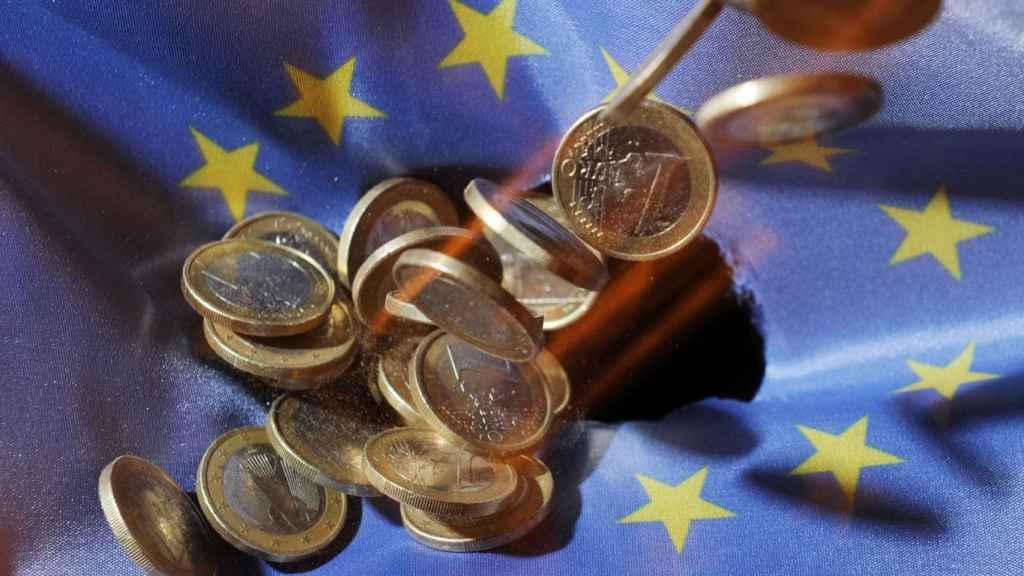 Monedas de euro sobre una bandera de la Unión Europea.