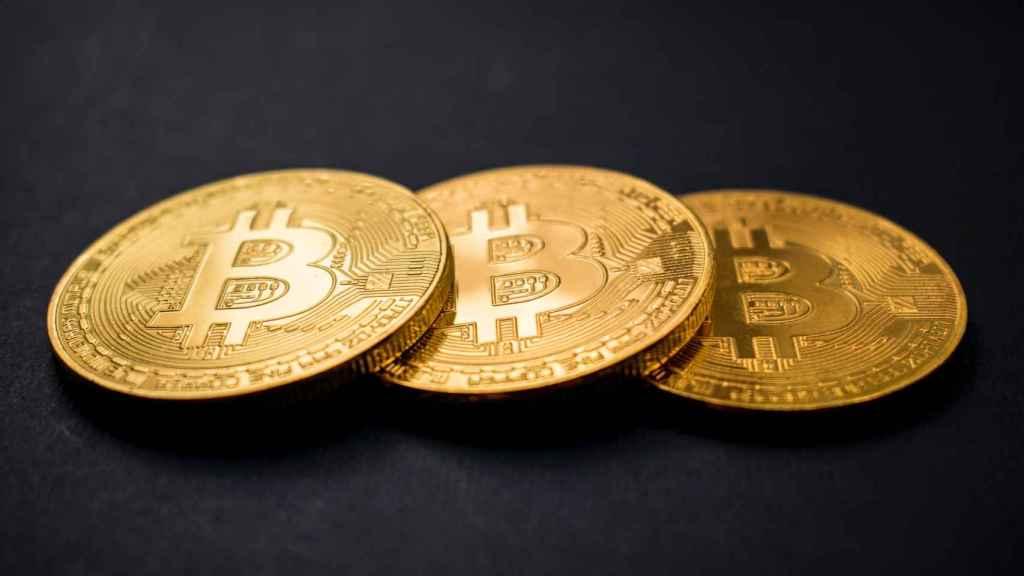 Tres monedas físicas representativas de bitcoins.