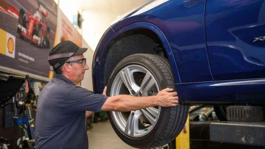 Un mecánico cambiando la rueda de un coche.