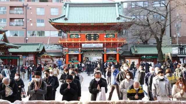 Varias personas rezando en Japón.