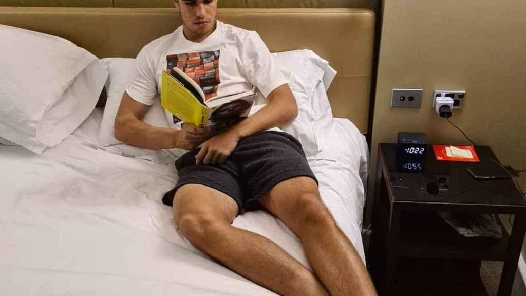 Carlos Alcaraz leyendo la biografía de Nadal en su habitación
