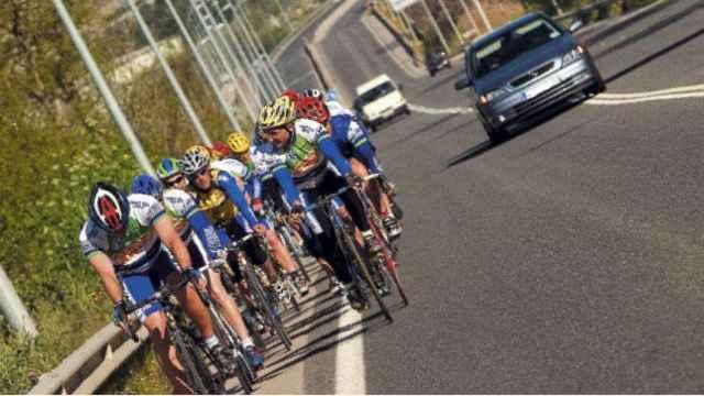 Un coche trata de adelantar un pelotón de ciclistas.
