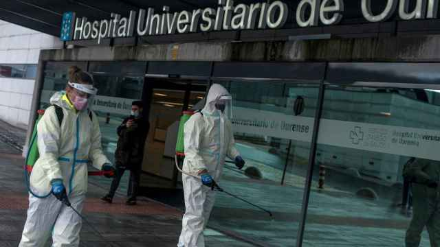 Empleados municipales desinfectan el acceso al Complejo Hospitalario Universitario de Ourense (CHUO) .
