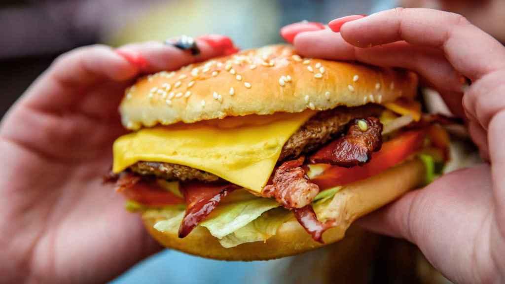 Una mujer sostiene una hamburguesa con muchos ingredientes.