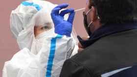 Una sanitaria haciendo una prueba PCR a un paciente.