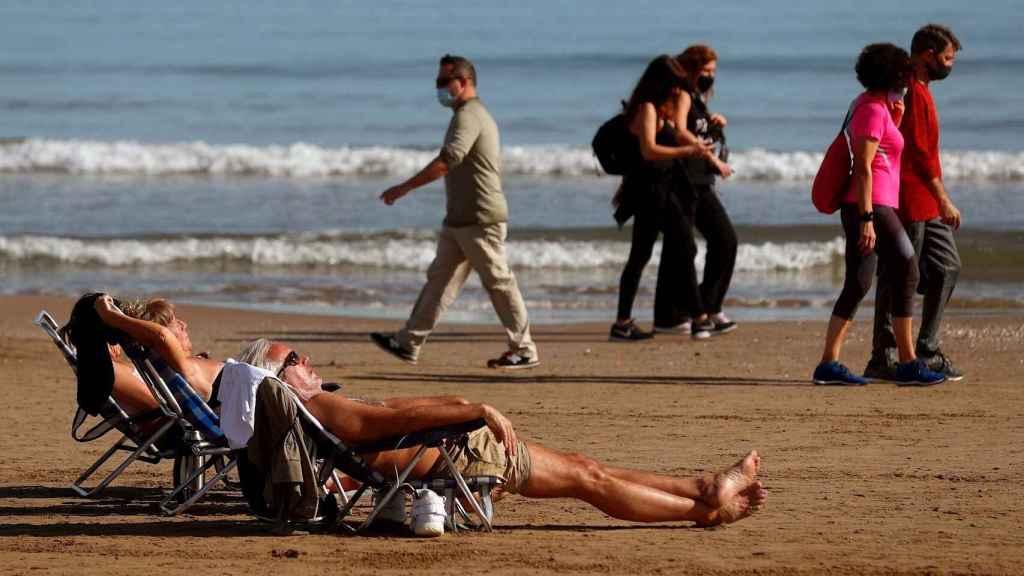 Varias personas toman el sol en la Playa de la Malvarrosa de Valencia el 27 de enero de 2021. EFE/Kai Försterling