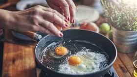 Una mujer fríe huevos en una sartén.