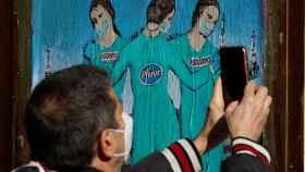 Un hombre fotografía un mural con 'las tres vacunas' en Barcelona.