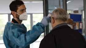 Personal sanitario toma la temperatura a una persona en la entrada de un centro.