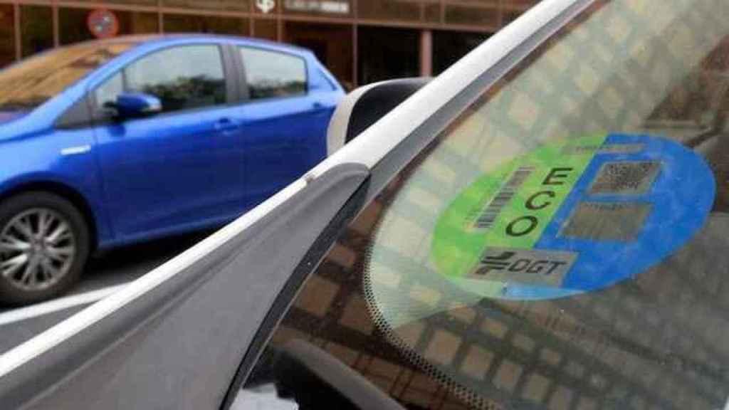 Un coche con la etiqueta ECO, de color azul y verde.