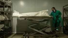 Una trabajadora de la funeraria Mémora traslada los restos mortales de una víctima de covid en el Tanatorio de Sancho d´Avila de Barcelona.