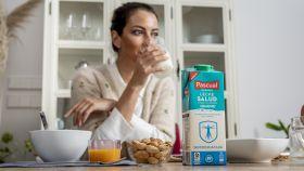 Una mujer tomando un vaso de leche Pascual Salud.