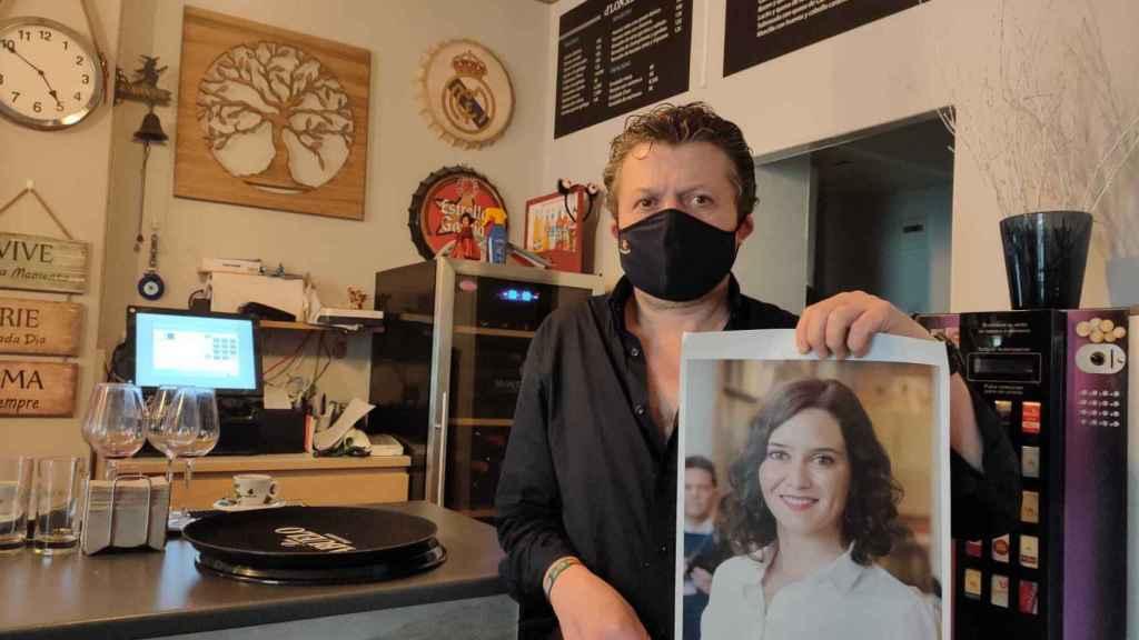 Jose posa con el retrato de la presidenta.