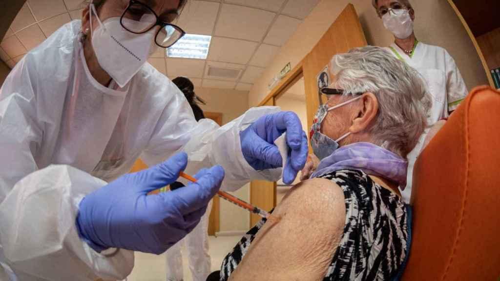 Una enfermera administra una vacuna a una señora mayor.