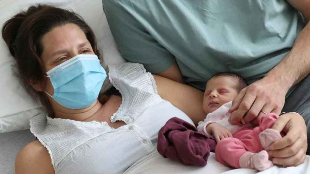 Una mujer que dio positivo antes de dar a luz, junto a su bebé en un hospital de Bruselas.