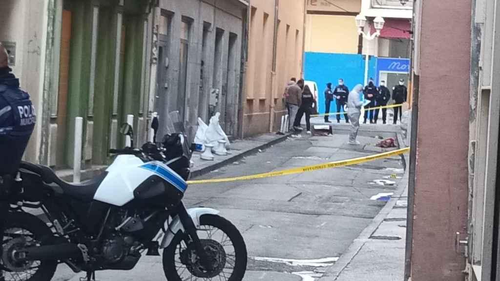 Los equipos de investigación franceses analizan el cartón ensangrentado en la calle.