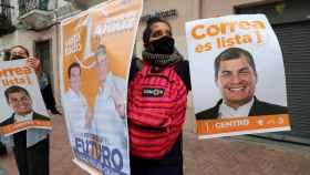 Simpatizantes del candidato a la presidencia Andrés Arauz (fuera de cuadro) participan en una caminata.
