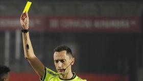 Sánchez Martínez enseña la tarjeta amarilla a Leo Messi