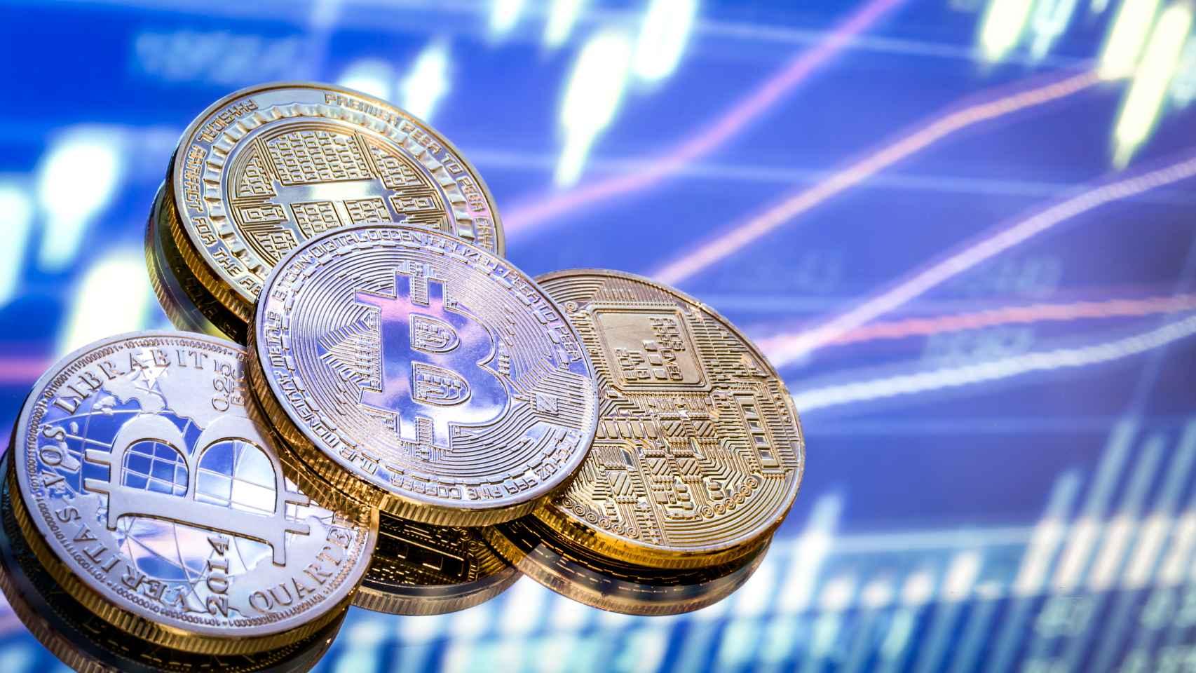 Unas monedas de bitcoin sobre gráficas de cotización.