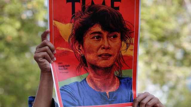 Un manifestante sujetando una pancarta con la cara de Aung San Suu Kyi.
