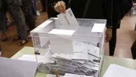 Un votante mete un sobre en una urna durante las elecciones en Barcelona. Efe
