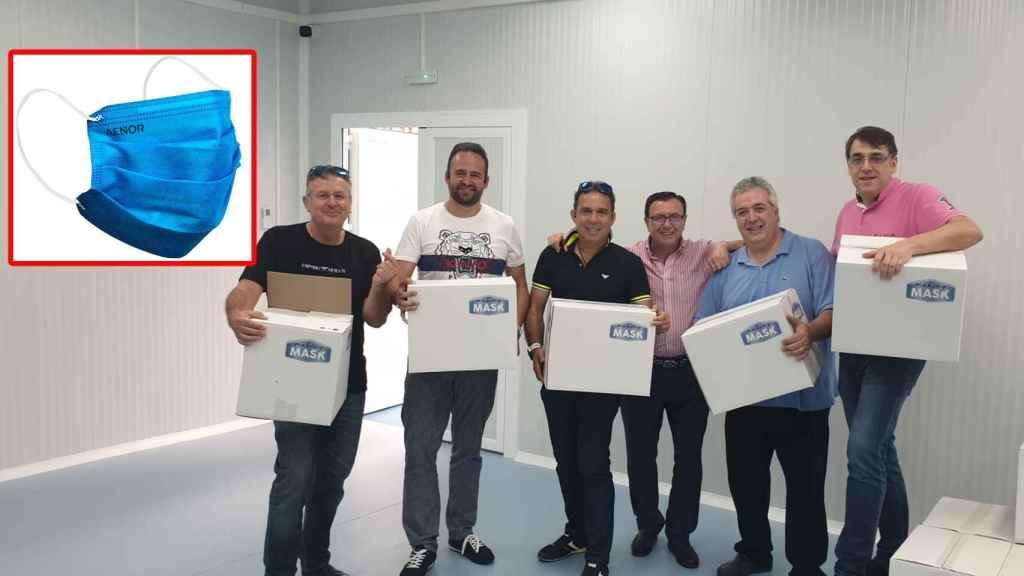 Cinco de los seis socios de Making Mask portando cajas de su mascarilla higiénicas reutilizable.