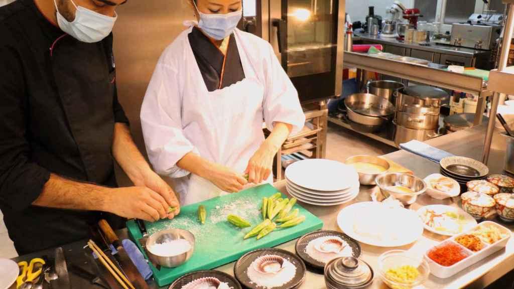 Yoko Hasei en su cocina, con uno de sus ayudantes.
