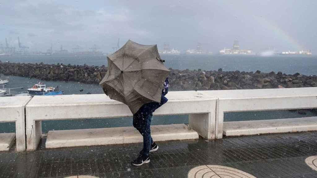 Una persona intenta avanzar ante el fuerte viento y la lluvia en la capital grancanaria. EFE/Ángel Medina G.