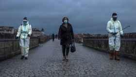Una viandante cruza el Puente Romano de Ourense mientras empleados municipales lo desinfectan. EFE/Brais Lorenzo.