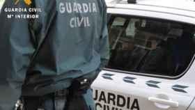 Un guardia civil delante de su vehículo.