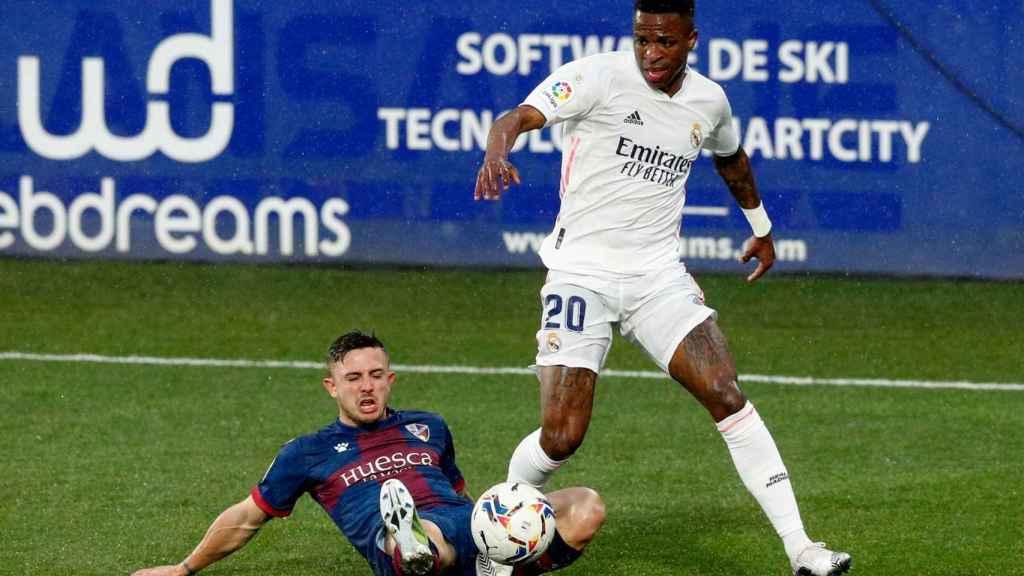 Vinicius evita la presión de un jugador del Huesca y avanza en la jugada